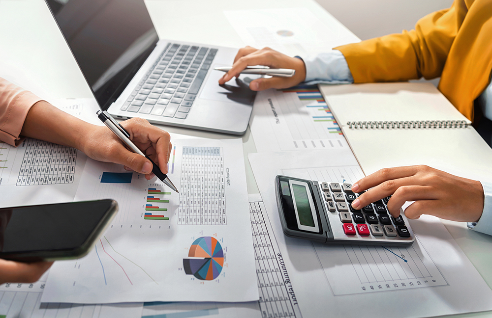 Investor working on charts and typing on calculator