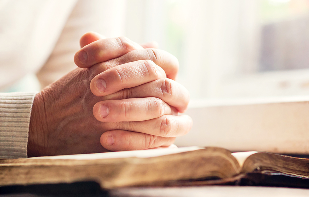 Person praying over book